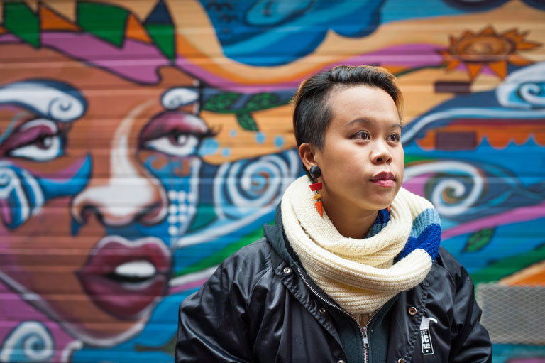 Kim Villagante stands beside the mural she helped create.